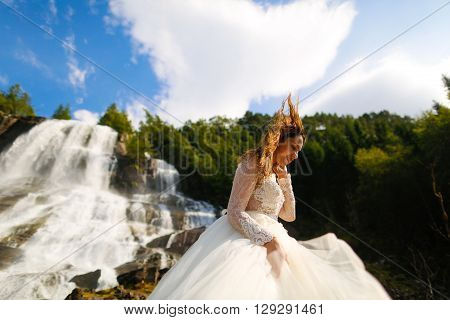 bride posing near the norvegian waterfall with blue skies