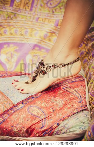 closeup of female foot with boho style foot jewelry on colorful pillows outdoor shot selective focus poster