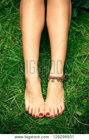 barefoot woman feet on grass with ankle bracelet above view
