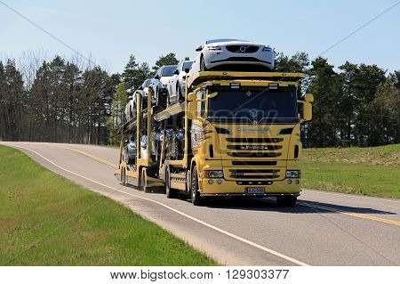 SALO, FINLAND - MAY 8, 2016: Yellow Scania R500 truck hauls a load of new cars along highway in South of Finland on a sunny day of spring.