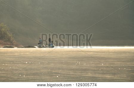 Two fishermen fishing in the misty morning at Mae Ngad Dam and Reservoir Chiang Mai Thailand poster
