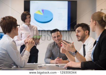 business people group on meeting at modern startup office, senior man  as leader looking on tablet and laptop presentation of his team
