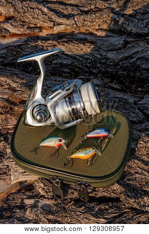 Fishing Reel And Various Kind Of Plastic Baits On The Natural Background.