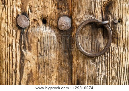 Old rustic weathered wooden door with a wrought iron ring handle and large old studs or nails close up background texture.