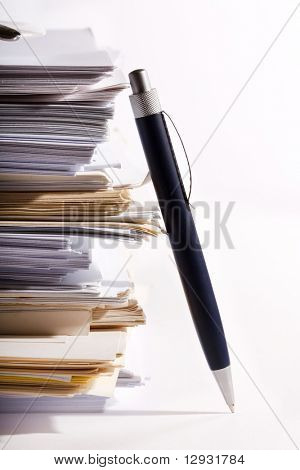 a pen near stack of paper
