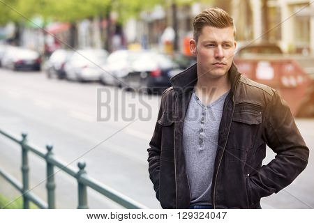 young blond man with leather jacket standing in the street