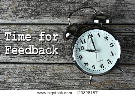 Black alarm clock on the rusty wooden table with word Time for Feedback