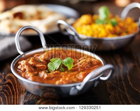 indian chicken curry in balti dish with Biryani in background