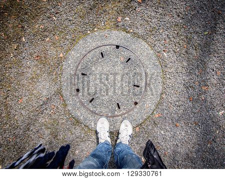 Man Standing Over Manhole Cover On Concrete Street