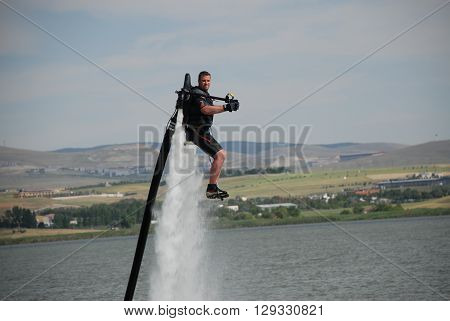 ANKARA/TURKEY-JUNE 24, 2012: A sportman over the Golbasi Mogan Lake with flyboard equipment during the spring festival. June 24, 2012-Ankara/Turkey