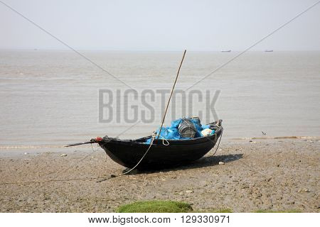 BAY OF BENGAL, WEST BENGAL, INDIA - DECEMBER 03: Boats of fishermen stranded in the mud at low tide on the coast of Bay of Bengal, India on December 03, 2012.