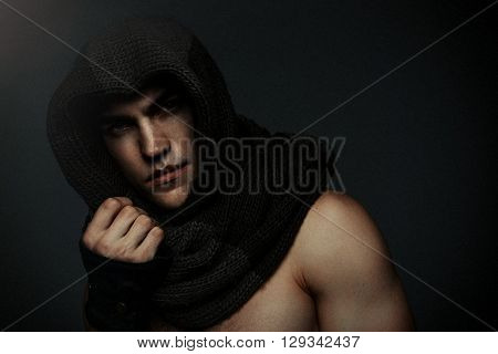 Fashion man portrait wearing knitted scarf on had on dark background