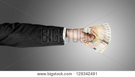Businessman's hand holding a stack of fifty euro notes isolated on white background.