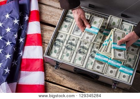 Hands holding bundles of dollars. Cash, hands and american flag. Time to make a stash. Big income can bring danger.