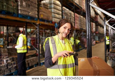 Woman using a barcode reader in a warehouse looks to camera