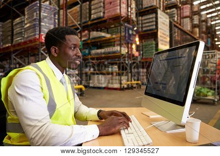 Manager at work in the on-site office of a warehouse