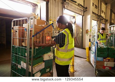 Man prepares and scans packages in a warehouse for delivery
