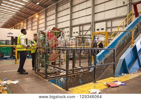 Warehouse staff with a roll cage of cardboard for recycling