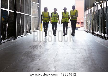 Four colleagues in reflective vests walking into a warehouse