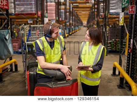 Female warehouse manager and man on tow tractor discuss