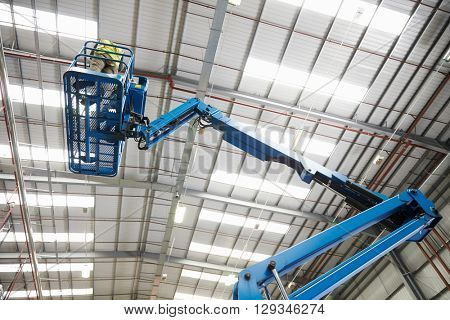 Low angle view of a cherry picker being used in a warehouse