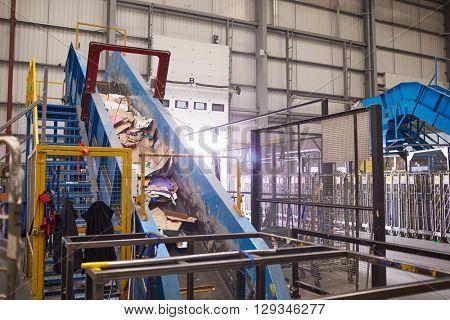 Waste cardboard entering recycling plant on a conveyor belt