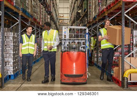 Staff at work in the aisle of a busy distribution warehouse