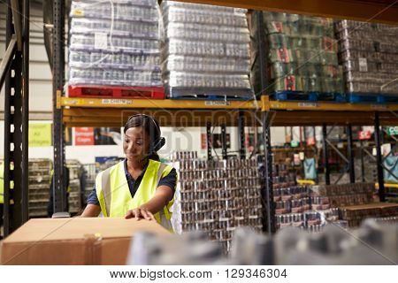 Woman using a barcode reader in a warehouse, wide shot