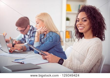 Technologies make life easier. Smiling young students sitting at the tables and studying with the help of new technologies