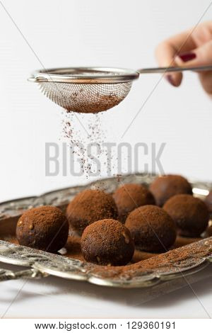Raw cacao balls and a woman hand adding cacao powder with a strainer