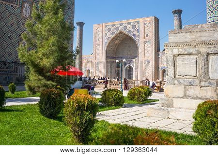 Samarkand Uzbekistan - April 18 2014: The garden leading to the Registan square with the wanderful mosque and madrassah