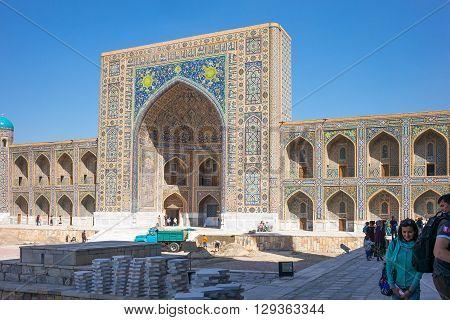Samarkand Uzbekistan - April 18 2014: People in Registan square with the Tilla Kari madrassah in the background