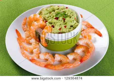 boiled tiger prawns tails on a white plate with guacamole sauce in a green bowl on a table mat on an old rustic table studio lights close-up