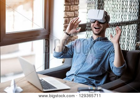 Open up  a new world. Overjoyed smiling handsome man sitting at the table and expressing gladness while using virtual reality device