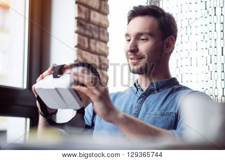 Smart technologies. Handsome delighted smiling man sitting at the table and holding virtual reality device while feeling glad