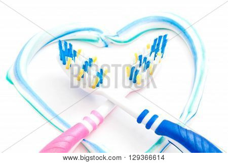 two toothbrushes in heart closeup on white background