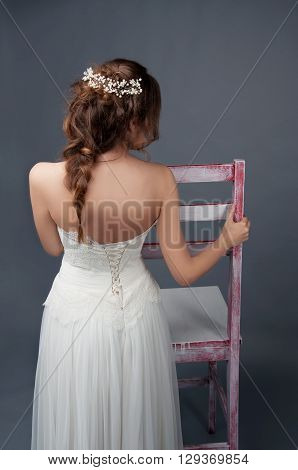 Bridal fashion. Brunette bride with pearl headpiece and white wedding gown view from the back.
