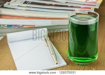 chlorophyll in glass and notebook on Brown tablecloth