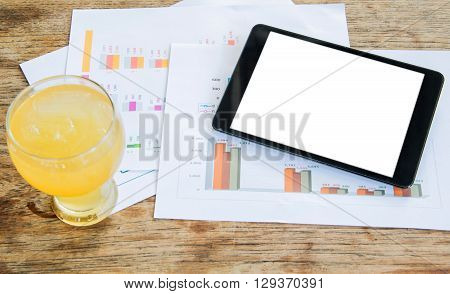 White display Tablet Cold glass lemonade Graph data analysis placed on wooden floor.