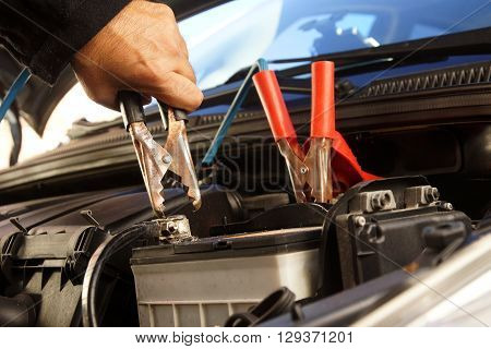 Hands installing battery booster cables on automotive battery