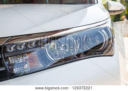 Closeup headlights of modern white car with LED daylight running lights