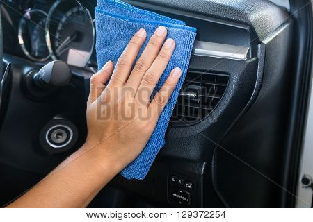 Hand with microfiber cloth cleaning Interior modern car.