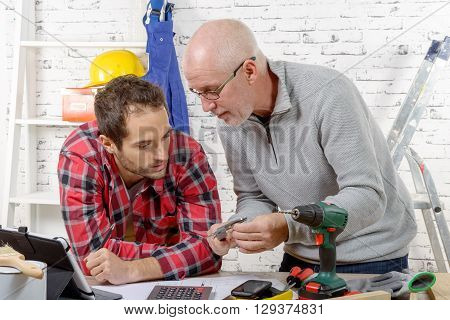 two technician examining a mechanical part in the workshop