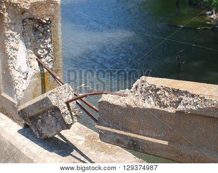 Broken concrete side rail of bridge over river.