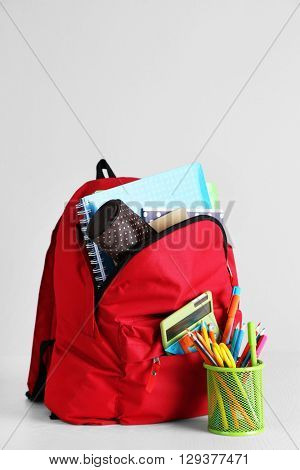 Backpack with school supplies on wooden table