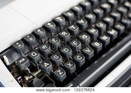 Detail view of the keys on a portable metal typewriter circa 1970 on the diagonal. Focus is on QWERTY. May be used to symbolize journalism or creativity or an antiquated method of communication.