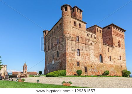 Medieval castle under blue sky in town of Grinzane Cavour in Piedmont, Northern Italy.