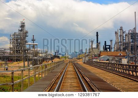 Oil and Gas Refinery Distillation Towers with Railroad Tracks and a Distant City