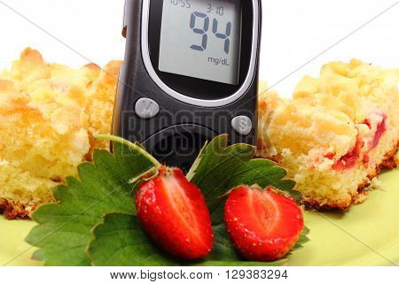 Glucose meter and pieces of fresh baked yeast cake with crumble and strawberries concept of diabetes sweet dessert