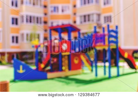 Defocused and blurred image for background of children's playground. Children's playground in the courtyard of a multistory building in sunny weather